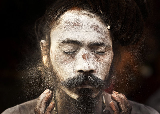 An Indian Sadhu, or Hindu holy man, smears sacred ash on his face at the Kamakhya Hindu temple ahead of the Ambubachi festival in Gauhati, India, Friday, June 21, 2019. The festival is held in celebration of the annual menstrual cycle of the Goddess Shakti at the Kamakhya Temple. the four-day festival will begin Saturday. (Photo by Anupam Nath/AP Photo)