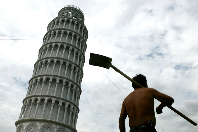 A Chinese worker walks past a replica of the leaning Tower of Pisa in Shanghai September 8, 2004. (Photo by Reuters/China Daily)