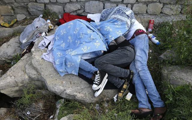 Migrants sleep together on the rocky beach at the Franco-Italian border near Menton, southeastern France Wednesday, June 17, 2015. European Union nations failed to bridge differences Tuesday over an emergency plan to share the burden of the thousands of refugees crossing the Mediterranean Sea, while on the French-Italian border, police in riot gear forcibly removed dozens of migrants. (AP Photo/Lionel Cironneau)