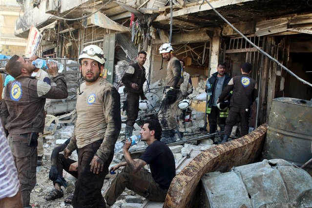 Civil defence members rest amid rubble of damaged buildings after an airstrike on the rebel-held Tariq al-Bab neighbourhood of Aleppo, Syria April 23, 2016. (Photo by Abdalrhman Ismail/Reuters)