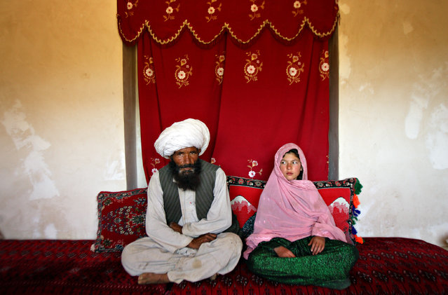 Faiz, 40, and Ghulam, 11, sit in her home prior to their wedding in rural Afghanistan, September 11, 2005. Ghulam said she is sad to be getting engaged as she wanted to be a teacher. Her favorite class was Dari, the local language, before she was made to drop out of school. Married girls are seldom found in school, limiting their economic and social opportunities. (Photo by Stephanie Sinclair/VII Photo Agency)