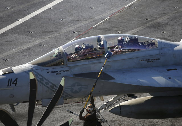 A U.S. Navy crew member wipes a window of a F/A-18 Super Hornet fighter on the deck of the USS Ronald Reagan, a Nimitz-class nuclear-powered super carrier, during a joint naval drill between South Korea and the U.S., in the West Sea, South Korea, October 29, 2015. (Photo by Kim Hong-Ji/Reuters)
