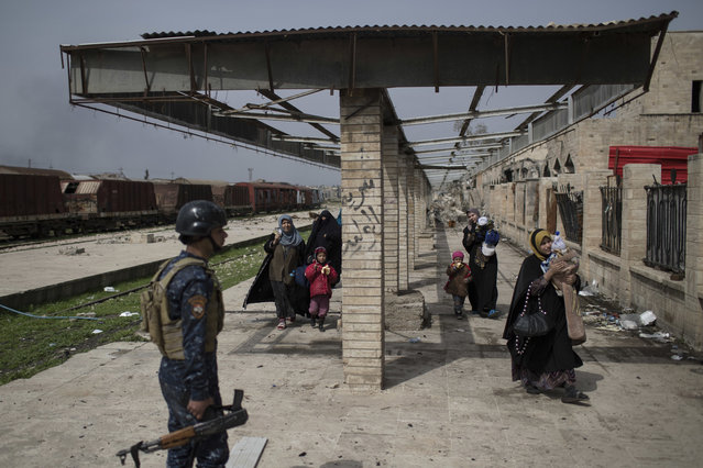 Iraqi civilians flee through a damaged train station during fighting between Iraqi security forces and Islamic State militants, on the western side of Mosul, Iraq, Sunday, March 19, 2017. (Photo by Felipe Dana/AP Photo)