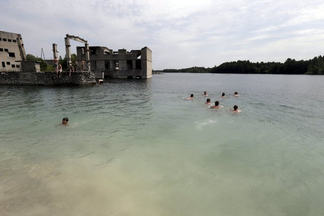 People swim near Murru prison, an abandoned Soviet prison, in Rummu quarry, Estonia, during hot weather July 4, 2015. (Photo by Ints Kalnins/Reuters)