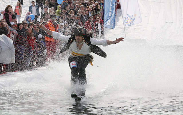 """A skier tries to cross a 26-metre long pool of water at the foot of a ski slope at the Bobrovy Log ski resort near Russia's Siberian city of Krasnoyarsk, April 20, 2014. 94 skiers and snowboarders took part in the annual """"Gornoluzhnik"""" amateur event to mark the end of the ski season at the Siberian resort. (Photo by Ilya Naymushin/Reuters)"""
