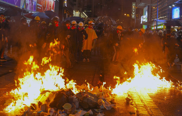 Protesters stand near burning items during a pro-democracy protest in causeway bay, Hong Kong, Saturday, August 31, 2019. Hundreds of people are rallying in an athletic park in central Hong Kong as a 13th-straight weekend of pro-democracy protests gets underway. (Photo by Vincent Yu/AP Photo)