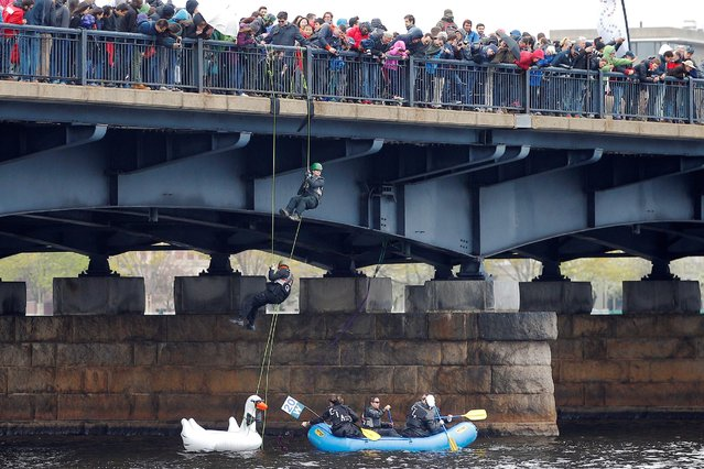 "Students rappel from the Mass Ave Bridge onto the ""One if By Land, 007 If By Sea – Getaway Raft"" in the Charles River, in Cambridge, Massachusetts, U.S. May 7, 2016 celebrating the 100th anniversary of the Massachusetts Institute of Technology's move from Boston across the Charles River to Cambridge. (Photo by Brian Snyder/Reuters)"