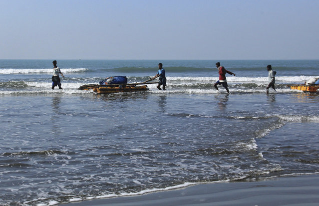 In this January 16, 2017, photo, Rohingya fishermen pull their rafts made of empty plastic containers along the shallow coastline of the Bay of Bengal in Tha Pyay Taw village, Maungdaw, western Rakhine state, Myanmar. (Photo by Esther Htusan/AP Photo)