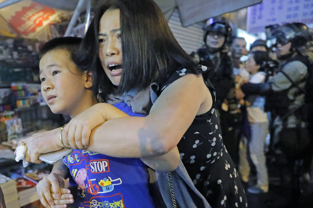 Mother and son leave as police arrive after pro-China supporters confronted with journalists in north point, at a local market of Hong Kong, Sunday, September 15, 2019. (Photo by Kin Cheung/AP Photo)