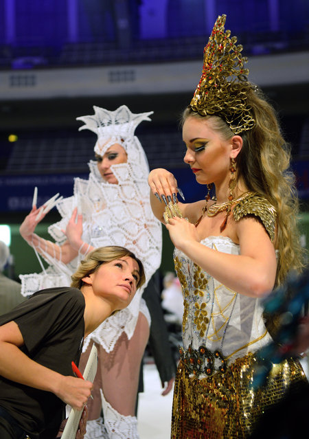 """A jury member rates a model's nails during the contest """"Haut Couture"""" of the OMC Hairworld World Cup on May 4, 2014 in Frankfurt am Main, Germany. (Photo by Thomas Lohnes/Getty Images)"""