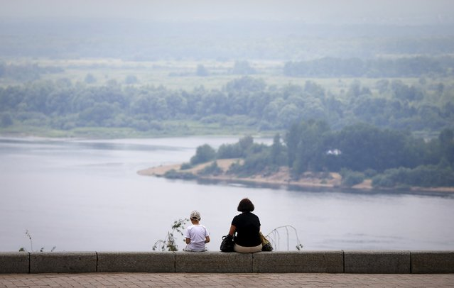 A woman and boy sit facing the Volga river in Nizhny Novgorod, Russia, July 10, 2015. (Photo by Maxim Shemetov/Reuters)