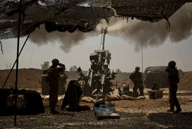 U.S. soldiers from the 82nd Airborne Division fire artillery in support of Iraqi forces fighting Islamic State militants from their base east of Mosul on Monday, April 17, 2017. The soldiers are from C Battery, 2nd Battalion, 319th Airborne Field Artillery Regiment. (Photo by Maya Alleruzzo/AP Photo)