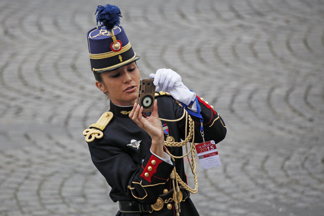A student of the French National gendarmerie officers school takes pictures before the start of the traditional Bastille Day military parade in Paris, France, July 14, 2015. (Photo by Mal Langsdon/Reuters)