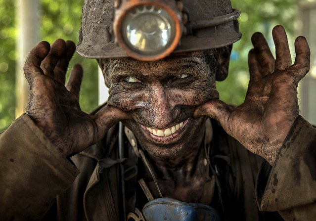 A coal miner smiles after finishing his shift at a coal mine outside Donetsk, Ukraine, on May 20, 2014. While steel workers in Mariupol joined anti-separatist actions, miners refused to take part in a planned protest against the Donetsk People's Republic. (Photo by Vadim Ghirda/Associated Press)