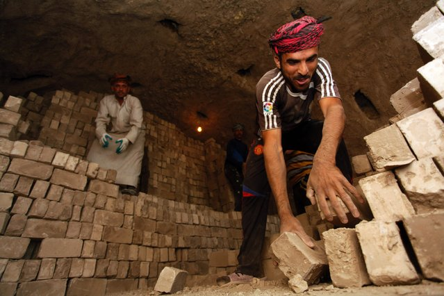 Workers stack bricks inside an oven at a brick factory near the central Iraqi shrine city of Najaf on May 16, 2017. (Photo by Haidar Hamdani/AFP Photo)