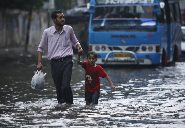 An Indian man wades through a flooded street with a child in Jammu, India, Tuesday, July 21, 2015. Vehicular movement on the 300 kilometers (186 miles) long Jammu-Srinagar national highway was thrown open on Sunday following heavy rainfall in the state, according to local reports. (Photo by Channi Anand/AP Photo)