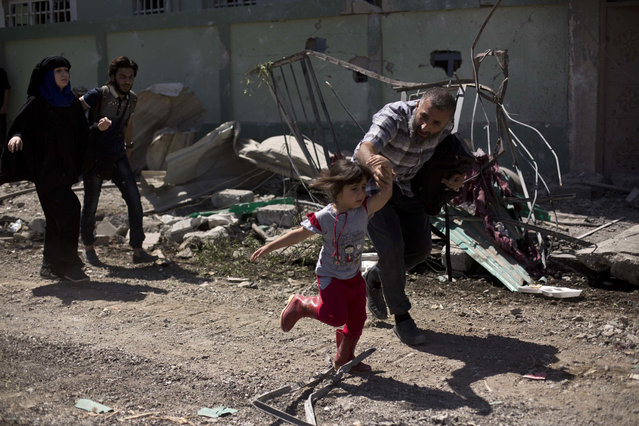 A man rushes his daughter to safety while fleeing the al-Rifai neighborhood as Iraqi special forces battle Islamic State militants, in western Mosul, Iraq, Wednesday, May 17, 2017. (Photo by Maya Alleruzzo/AP Photo)