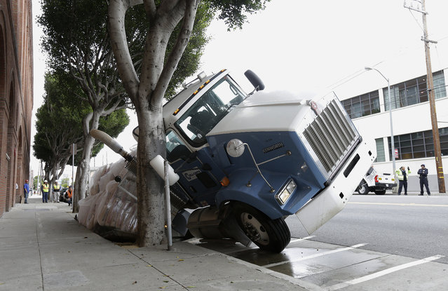 A big rig truck is stuck in a sinkhole in San Francisco, Friday, May 5, 2017. A truck driver escaped unharmed early Friday after a massive sinkhole started swallowing his big rig on a San Francisco street. (Photo by Jeff Chiu/AP Photo)