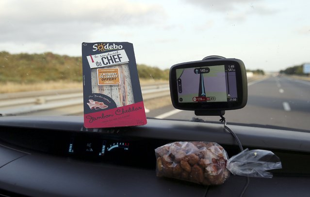A sandwich that is a photographer's dinner sits on the dashboard of a car during the transfer on the highway after the 9th stage of the Tour de France cycling race from Vannes to Plumelec, France, July 12, 2015. (Photo by Stefano Rellandini/Reuters)