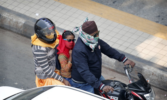 A family covers their face with clothe to save themselves from pollution as they ride on a motorcycle in New Delhi, India, Tuesday, November 12, 2019. A thick haze of polluted air is hanging over India's capital, with authorities trying to tackle the problem by sprinkling water to settle dust and banning some construction. The air quality index exceeded 400, about eight times the recommended maximum. (Photo by Manish Swarup/AP Photo)