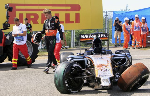 Force India Formula One driver Nico Hulkenberg of Germany walks past his car after a crash during the Hungarian F1 Grand Prix at the Hungaroring circuit, near Budapest, Hungary July 26, 2015. (Photo by Bernadett Szabo/Reuters)