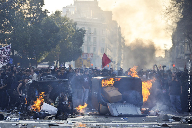 Demonstrators set fire to garbage containers during heavy clashes with riot police during a 24-hour strike on March 29, 2012 in Barcelona, Spain