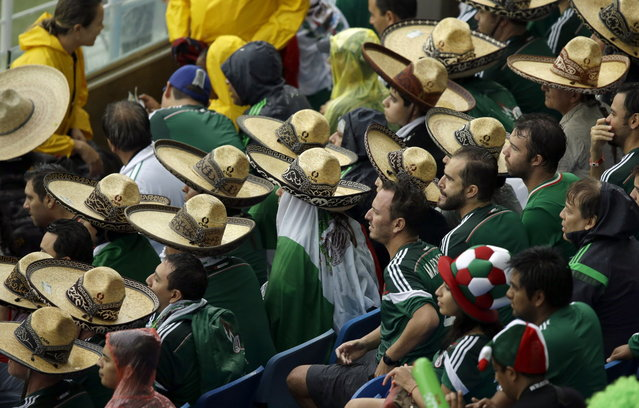 """Mexican fans wearing the traditional Mexican """"sombreros"""" watch the group A World Cup soccer match between Mexico and Cameroon in the Arena das Dunas in Natal, Brazil, Friday, June 13, 2014. (Photo by Hassan Ammar/AP Photo)"""