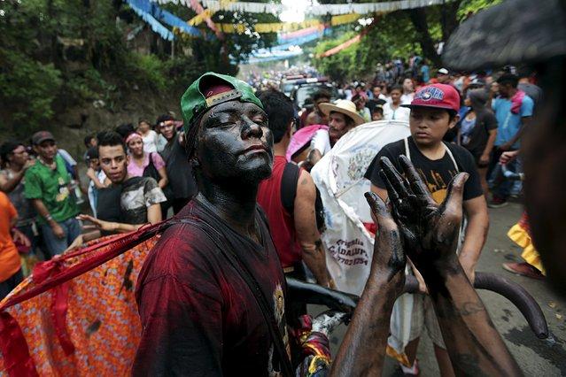 A devotee covered in motor oil takes part in celebrations honouring the patron saint of Managua, Santo Domingo de Guzman in Managua, Nicaragua, August 1, 2015. (Photo by Oswaldo Rivas/Reuters)