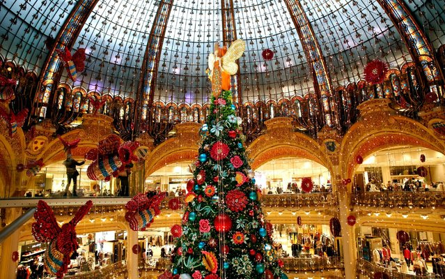 A giant christmas tree stands in the center of the Galeries Lafayette department store in Paris, Thursday, December 19, 2019. (Photo by Thibault Camus/AP Photo)