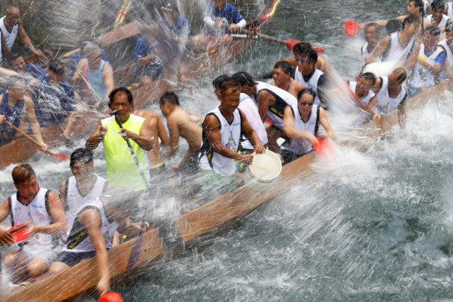 Participants splash water during a ceremony in between races during Tung Ng or Dragon Boat Festival at Aberdeen fishing port in Hong Kong June 9, 2016. (Photo by Bobby Yip/Reuters)