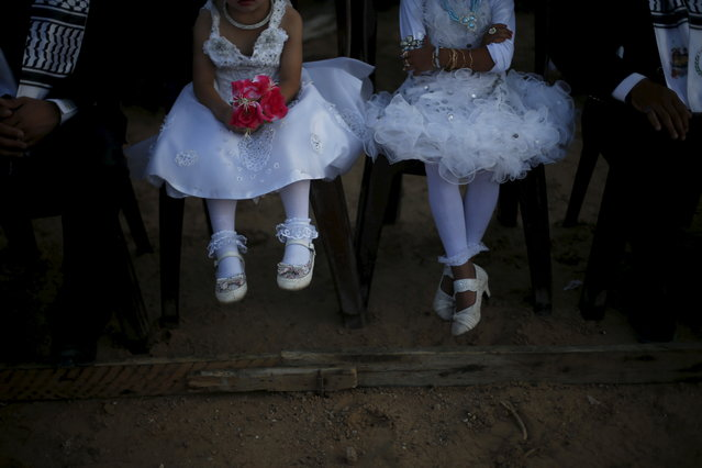 Girls accompany grooms as they sit separate from the brides during a mass wedding for 150 couples in Beit Lahiya town in the northern Gaza Strip, July 20, 2015. (Photo by Suhaib Salem/Reuters)