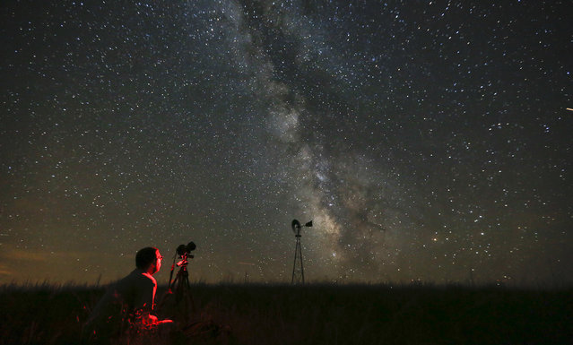 In this Wednesday, July 23, 2014 file photo, Omaha photographer Lane Hickenbottom photographs the night sky in a pasture near Callaway, Neb. With no moon in the sky, the Milky Way was visible to the naked eye. More than one-third of the world's population can no longer see the Milky Way because of man-made lights, according to a scientific paper by Light Pollution Science and Technology Institute's Fabio Falchi and his team members, published on Friday, June 10, 2016. (Photo by Travis Heying/The Wichita Eagle via AP Photo)