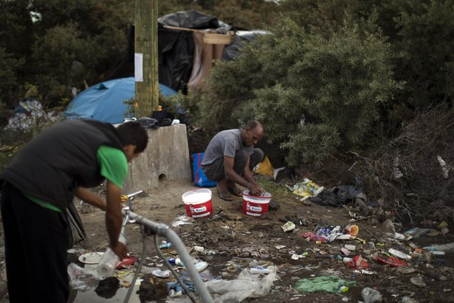 A migrant washes his clothes as another collects water, at a camp near Calais, northern France, Tuesday, August 4, 2015. (Photo by Emilio Morenatti/AP Photo)