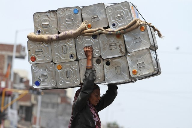 An Indian woman carries empty oil tins on her head, meant for recycling in Ahmadabad, India, Tuesday, July 1, 2014. (Photo by Ajit Solanki/AP Photo)