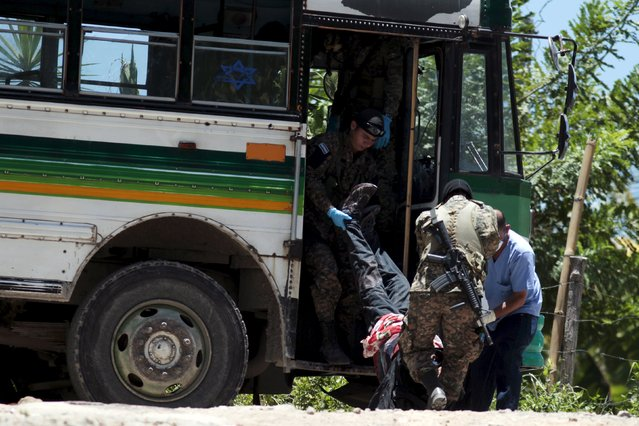 Soldiers help to unload one of four people murdered in a bus that was attacked earlier by suspected gang members in San Pedro Perulapan, El Salvador August 5, 2015. Four people were killed and seven more were wounded in a deadly attack this morning by gang members, according to local media. (Photo by Jose Cabezas/Reuters)