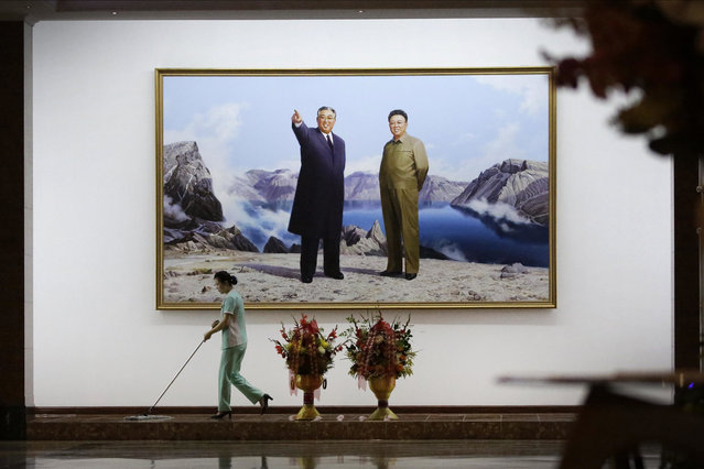 A hotel staff member mops the floor where a picture featuring portraits of the late North Korean leaders Kim Il Sung, left, and Kim Jong Il decorates the lobby wall Monday, June 19, 2017, in Pyongyang, North Korea. (Photo by Wong Maye-E/AP Photo)