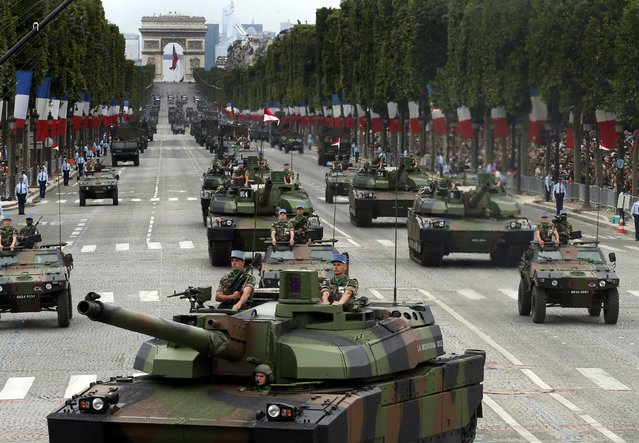 Tanks rumble down the Champs Elysee during the traditional Bastille Day parade in Paris, July 14, 2014. (Photo by Benoit Tessier/Reuters)