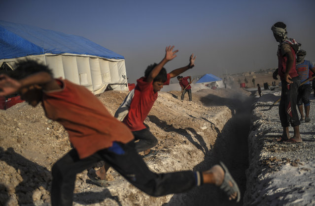 Boys play as workers dig a trench for the sewage system of a temporary camp for displaced people near the northern Syrian village of Ain Issa on July 19, 2017, during an offensive by Syrian Democratic Forces, a Kurdish-Arab alliance, to retake Raqa from Islamic State (IS) group fighters. The SDF have been pressing an operation to capture the jihadist stronghold since last year, and they penetrated the city in June. (Photo by Bulent Kilic/AFP Photo)