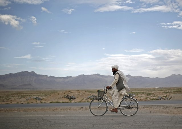An Afghan man rides a bicycle on the outskirts of Kabul city, Afghanistan July 30, 2015. (Photo by Ahmad Masood/Reuters)