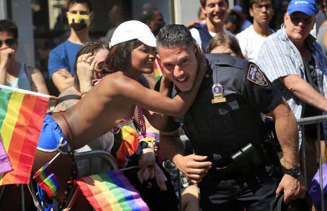 Tina Hitscherich surprises a police officer with a kiss during the NYC Pride Parade in New York, Sunday, June 26, 2016. With a moment of silence followed by the roar of motorcycles, New York City's gay pride parade kicked off Sunday, a celebration of barriers breached and a remembrance of the lives lost in the massacre at the gay nightclub in Orlando. (Photo by Seth Wenig/AP Photo)