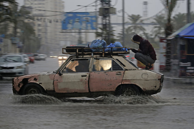 A car drives through a flooded road following heavy rain in Gaza City on December 27, 2019. (Photo by Mohammed Abed/AFP Photo)