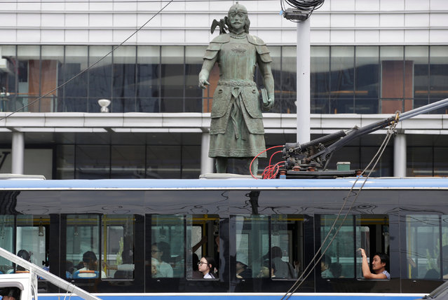 A bus drives past a statue of Marco Polo in downtown Ulaanbaatar, Mongolia, June 28, 2016. (Photo by Jason Lee/Reuters)