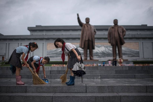 "Students clean the steps in front of the statues of late North Korean leaders Kim Il-Sung and Kim Jong-Il at Mansu hill as the country marks ""Victory Day"" in Pyongyang on July 27, 2017. July 27, which is the 64th anniversary of the signing of the Korean Armistice Agreement, is a public holiday in the nuclear-armed North and celebrated as Victory Day. (Photo by Ed Jones/AFP Photo)"