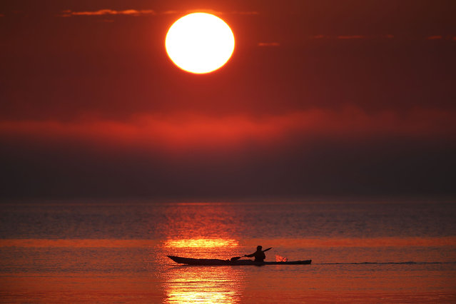 A Kayaker paddles near the Frankston foreshore as the sun sets over the low lying cloud of fog on July 22, 2014 in Melbourne, Australia. Low temperatures and heavy fog hit Melbourne on Tuesday morning and again on Wednesday, causing Tuesday's flight delays. (Photo by Michael Dodge/Getty Images)