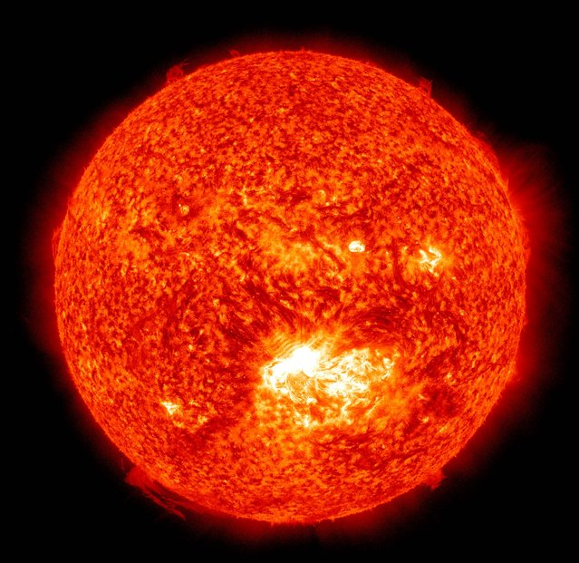 The 304 Angstrom wavelength, which is typically colorized in red  shows a solar flare, lower center, erupting from the sun