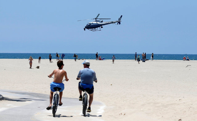 A Los Angeles Police Department helicopter flies low over the beach in the Venice neighborhood of Los Angeles, California U.S., July 6, 2016. (Photo by Mario Anzuoni/Reuters)