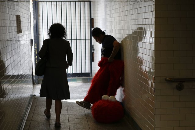 Jorge, an immigrant from Mexico, gets dressed as the Sesame Street character Elmo inside of a subway station in Times Square, New York July 30, 2014. (Photo by Eduardo Munoz/Reuters)