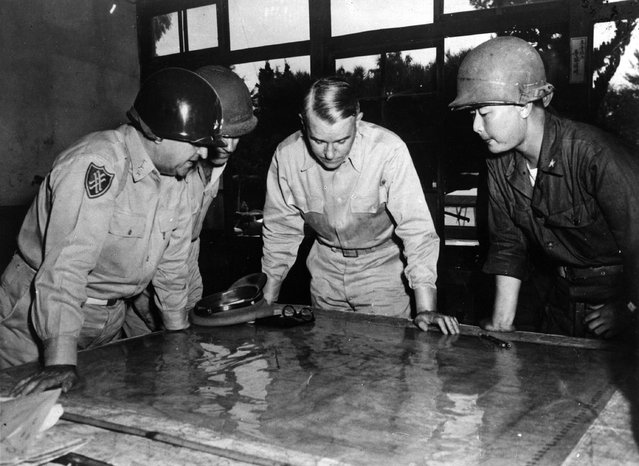 United States Army Chief of Staff General Collins studying a map of the front line during the battle for Korea, with Lieutenant General Walker, Brigadier General Farrell and Korean Brigadier General Paik, 1950.  (Photo by Keystone)