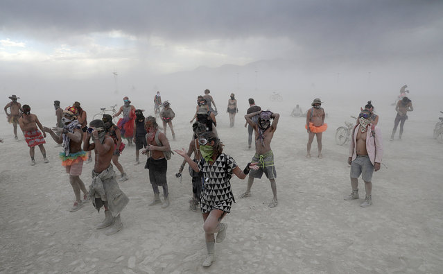 Burning Man participant dance to the music of an art car in the midst of a driving desert dust storm at the Burning Man festival in the Black Rock Desert of Nevada, U.S. August 30, 2017. (Photo by Jim Urquhart/Reuters)