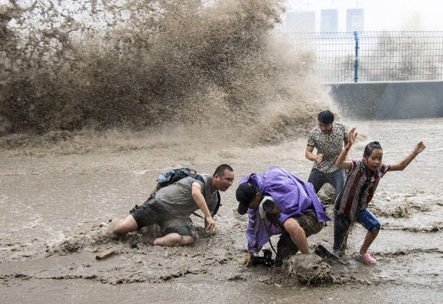 Visitors fall to the ground after being hit by waves caused by a tidal bore which surged past a barrier on the banks of Qiantang River, in Hangzhou, Zhejiang province August 13, 2014. (Photo by Reuters/Stringer)
